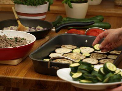 Przygotowywanie musaki - warstwa z bakłążana i cukinii